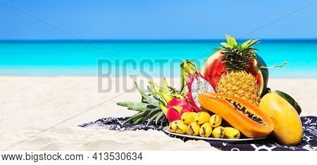 Panorama Of Fresh Different Tropical Fruits Placed On The Beach With Blue Sky And Sea Background. Su