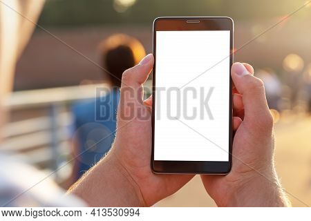 Man Uses His Mobile Phone Outdoor, Close Up. Mockup Image Blank White Screen Cell Phone. Men Hand Ho