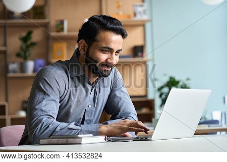 Smiling Indian Business Man Working On Laptop At Home Office. Young Indian Student Or Remote Teacher