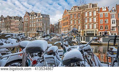 Snowy bikes in Amsterdam in winter in the Netherlands