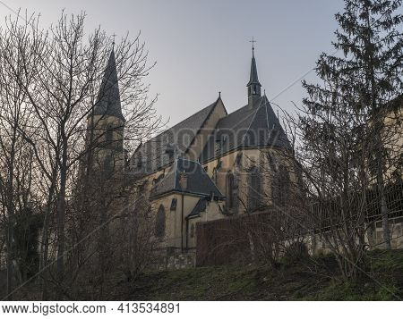 View Of Gothic Church Of Saint Apolinar In Czech Kostel Sv. Apolinare With Bare Trees At Old Prague