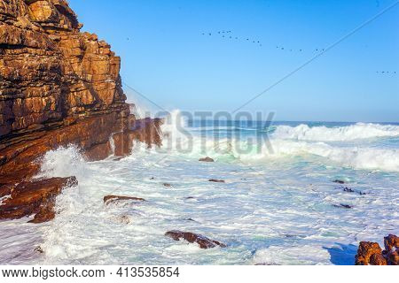 White foam of the ocean surf. South Africa. Powerful ocean surf. Cape of Good Hope at the southern tip of the Cape Peninsula. Bright sunny summer february day