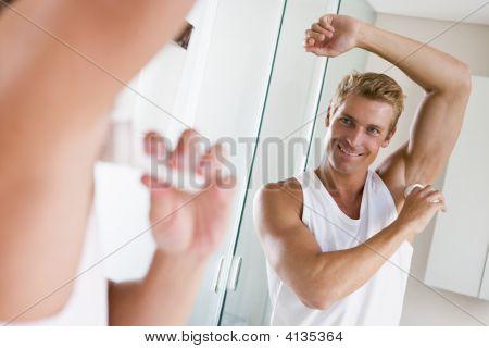 Man In Bathroom Applying Deodorant Smiling