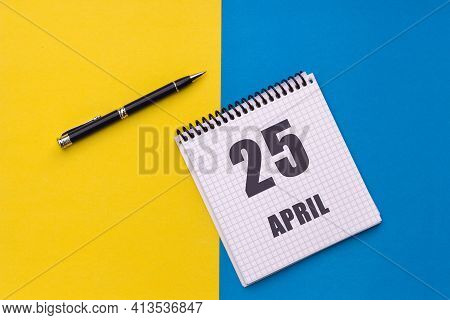 April 25th. Day Of 25 Month, Calendar Date. A Notebook With A Spiral And A Pen Lies On A Yellow-blue