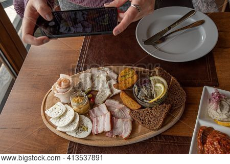 Hands Taking Photo Of Meze Appetizers With Smartphone. Local Food Mezze Dish With Cheese, Meat, Baco