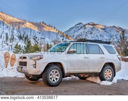 Fort Collins, CO, USA - March 17, 2021:  Toyota 4Runner SUV (2016 Trail edition) at trailhead parking with classic snowshoes in the Poudre Canyon.