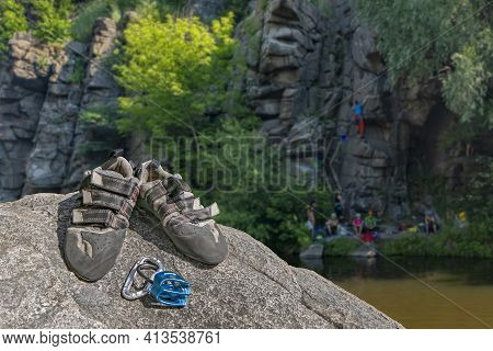 Climbing Gear Equipment On Rock On Blurred Background Of Climbing People At River Canyon. Climb Shoe