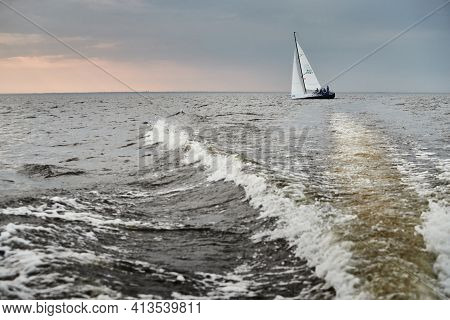 Russia, St.petersburg, 05 September 2020: The Lonely Sailboat In A List Goes By Sea, The Sky Of Pink