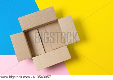 One Open Empty Cardboard Box On Geometric Pink, Blue, Yellow Background. Top View
