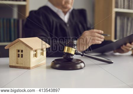 Closeup Of Judges Gavel And Little Wooden Toy House Placed On Table In Court Of Law