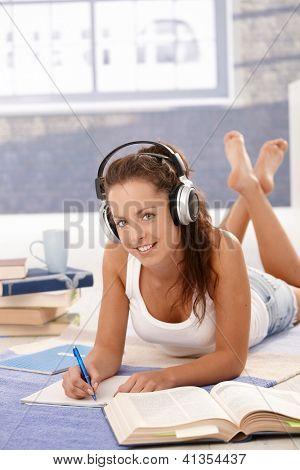 Hübsches Mädchen zu Hause Handauflegen Stock, lernen die Verwendung von Kopfhörern, lächelnd.