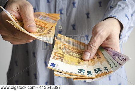 Man Holds Money In His Hands. Cash In Euro For Payment Or Exchange. Male Counts Salary In Euro Bankn