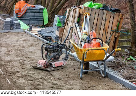 Construction Yellow Wheelbarrow, Petrol Vibrating Plate And The Necessary Tool For Paving The Sidewa