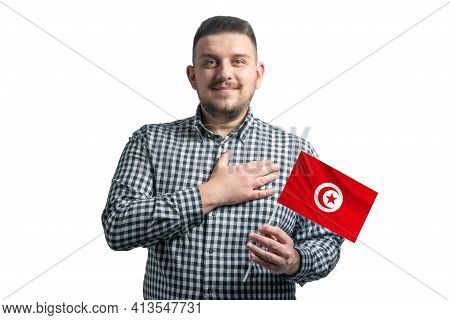 White Guy Holding A Flag Of Tunisia And Holds His Hand On His Heart Isolated On A White Background W