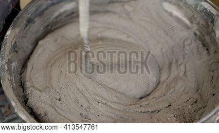 The Worker Mixes The Mortar. Wet Concrete Or Motrar Mixing Texture. Gray Mortar, Concrete Surface. T