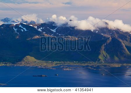 Scenic mountain peaks on Lofoten islands in Norway covered with clouds with small fishing villages on the coast poster
