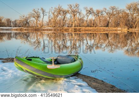 inflatable whitewater kayak on a lake shore with blue heron rookery in background, Fort Collins, Colorado, winter or early spring scenery