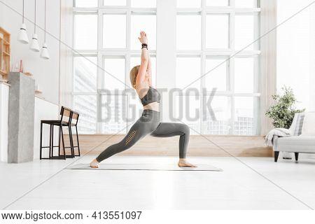 An Adult Woman Practices Ashtanga Vinyasa Yoga At Home On The Background Of A Window. Virabhadrasana