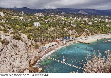 Suspension Bridge To The Diva Rock, Black Sea Coast, Near Yalta, Crimea. Panorama Of The Town Of Sim