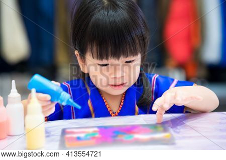 Asian Girl Doing Crafts With Watercolor. Child Was Holding Blue Bottle With Watercolor Inside. Child