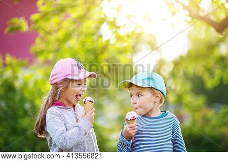 Happy Children Eating Ice Cream Outdoors In Summer In Garden. Portrait Of A Funny Cute Boy And Girl