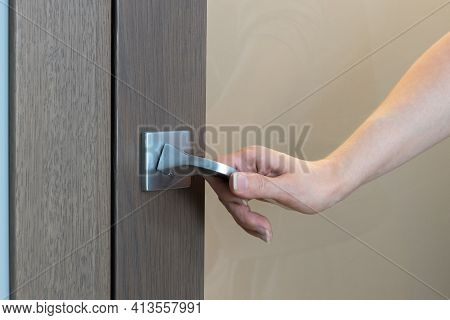 Woman Opens Or Closes Door. Close-up Of Hand Opening Door, Unrecognizable Person. Only Hand Is Visib