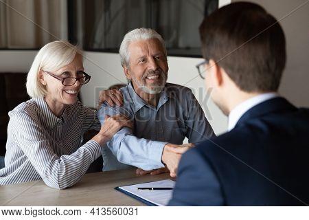 Smiling Older Couple Clients Handshake Relator At Meeting
