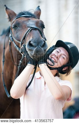 Portrait Of Funny Chestnut Horse Snout On Girl's Coach Hands. Colored Outdoors Vertical Summertime I