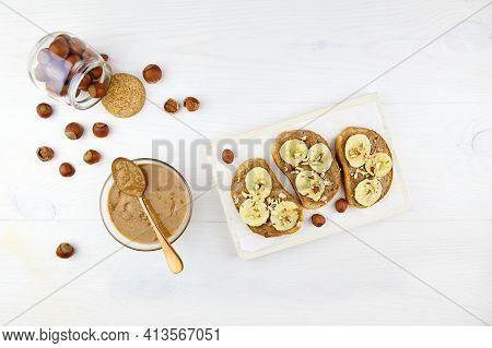 Homemade Raw Organic Hazelnut Paste. Toasts With Hazelnut Butter And Banana. Hazelnuts In Jar On Woo