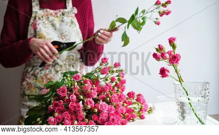 Close-up Of A Florist Woman's Hand In A Flower Apron Cuts The Stems Of A Bouquet Of Pink Roses With