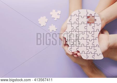 Adult And Children Hands Holding Brain With Puzzle Paper Cutout, Autism, Memory Loss, Dementia, Epil