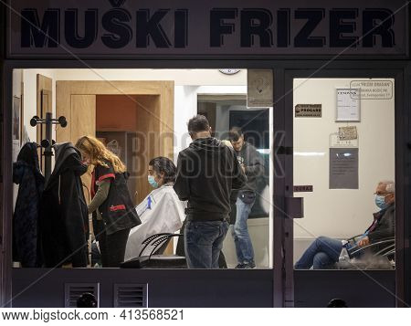 Belgrade, Serbia - October 10, 2020: Hairdresser, A Woman, Cutting The Hair Of A Male Client In A Ha