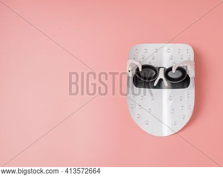 Led Light Therapy Facial Mask On Pink Background. Home Skincare And Me Time Concept. Light Rejuvenat