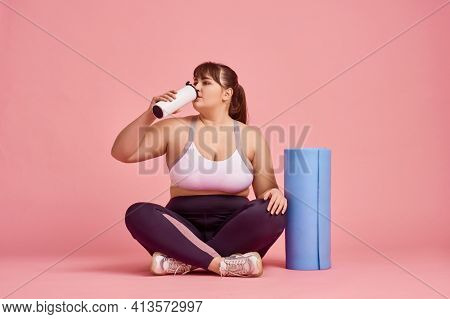 Overweight woman drinks water, body positive
