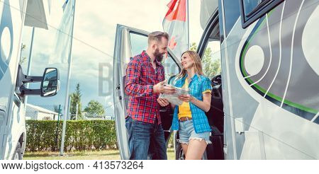 Couple choosing their next vacation route on map on yard of rv dealer