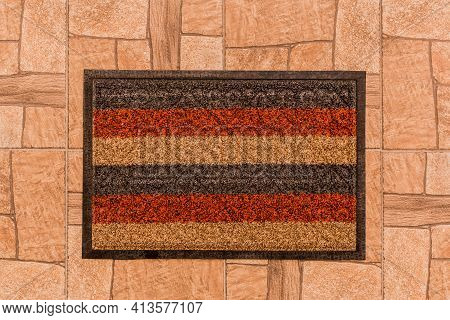The Rug For The Feet Of Guests In The Hallway On The Background Of A Brown Tiled Floor Texture Backg