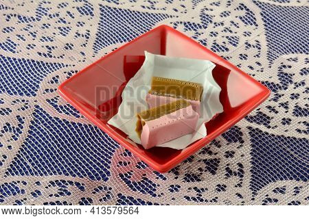 Strawberry And Licorice Caramels In Candy Wrappers In Red Candy Dish On Lace