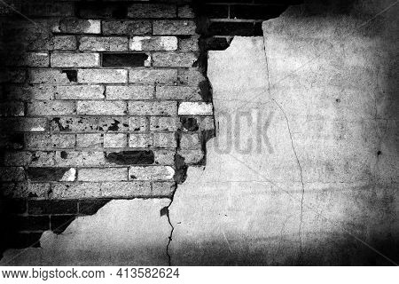 Old stucco wall with cracked cracks plaster and bricks texture in black and white grunge