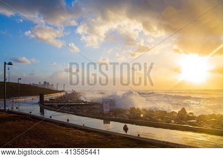 Embankment in Tel Aviv. Israel. Sunset. Powerful winter surf takes off with snow-white foam. Windy sunny day on the Mediterranean coast. Winter storm in the Mediterranean