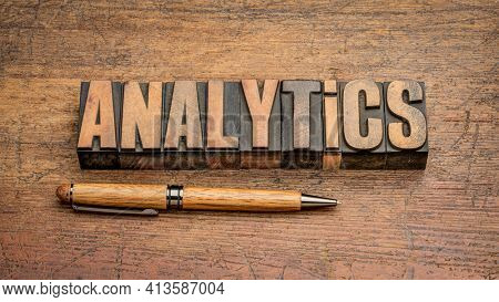 analytics word abstract in vintage letterpress wood type against weathered wooden background, business, data, statistics and research concept