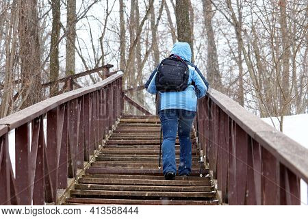 Woman With Walking Sticks And Backpack Climbs Up The Wooden Stairs During Snow. Nordic Walking At Ea