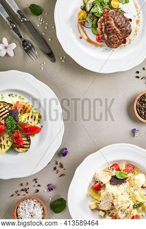 Food on luxury white plate. Beef steak, grilled vegetable and chicken caesar salad on grey textured table. Restaurant dinner gourmet menu, delicious lunch