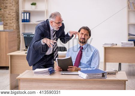 Old male boss and young employee working in the office