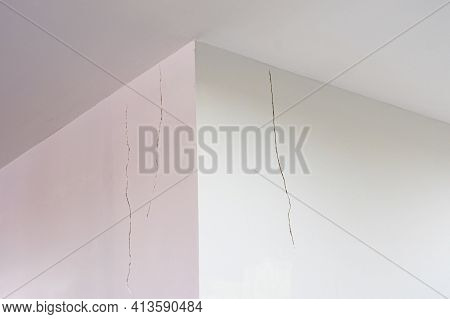 White Painted Cement Wall With Cracked Grooves Near The Ceiling