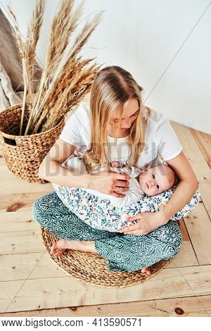 A Beautiful Young Mother With Long Blonde Hair And A Daughter Of 2-3 Months Are Resting In The Floor