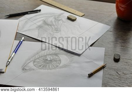 Drawings Made By A Pencil Lie On A Brown Wooden Table. Horse Portrait And Human Eye Drawn On White P