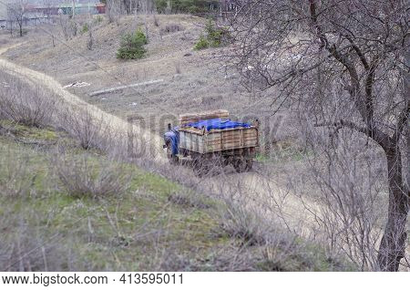 Top View At An Angle Of An Old Dump Truck Driving On A Dirt Road In A Ravine. A Truck With A Blue Ca