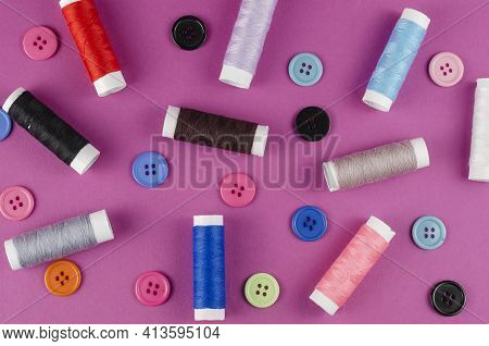 Multicolored Thread Spools And Buttons On Purple Background. A Set Of Thread. Ten Spools. Random But
