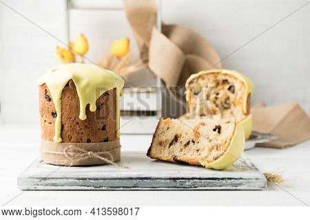 Easter Cake With Raisins, Dried Apricots And Prunes Covered With Yellow Icing And Its Piece On A Woo