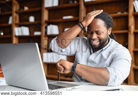 Young African American Guy Totally Forgot About A Business Meeting, Sitting At The Desk And Working